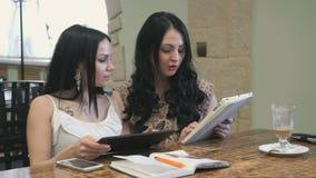 Olhar de duas meninas em imagens na tabuleta digital vídeos de arquivo