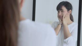 Olhar de sorriso da mulher asiática do retrato da beleza no espelho de verificar a pele caucasiano com o bem-estar filme
