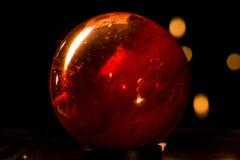 Olhar de vidro da esfera da bola vermelha como Marte com bokeh imagem de stock