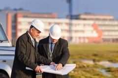 Olhar do homem de dois arquitetos na planta da construção imagem de stock royalty free