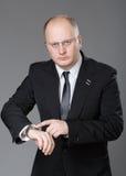 Olhar do homem de negócios o seu relógio fotografia de stock royalty free