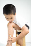 Olhar do menino na ferida em seu pé Fotos de Stock