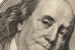 Olhar do ` s de Benjamin Franklin em cem notas de dólar r fotografia de stock