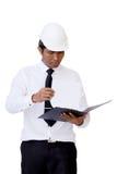 Olhar do trabalhador da construção no relatório na prancheta Imagens de Stock