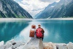Olhar dos pares dos viajantes no lago da montanha Curso e conceito ativo da vida com equipe fotografia de stock royalty free
