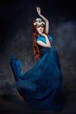 Olhar fabuloso da menina do ruivo, vestido longo azul, composição brilhante e pestanas grandes Mulher feericamente misteriosa com Foto de Stock Royalty Free