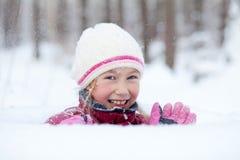 Olhar feliz da menina fora do snowdrift fotos de stock royalty free