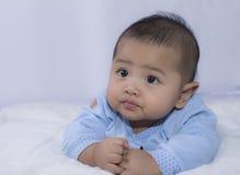 Olhar fixamente do bebê de três luas do thinkin na cama branca Imagens de Stock