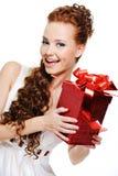 Olhar fêmea feliz bonito para fora com caixa vermelha Foto de Stock
