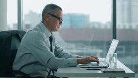 Olhar idoso do homem de negócios no telefone e trabalho com o computador no escritório moderno vídeos de arquivo