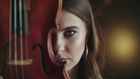 Olhar misterioso e apaixonado na câmera da menina com o violino na cara filme