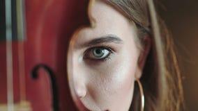 Olhar misterioso e apaixonado na câmera da menina com o violino na parte da cara filme