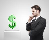 Olhar novo do homem de negócios nos sig verdes do dólar americano Imagens de Stock Royalty Free