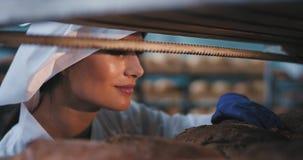 Olhar perfeito do close up do padeiro da jovem mulher em uma padaria que cheira excitou o pão cozido fresco e toma algum do filme