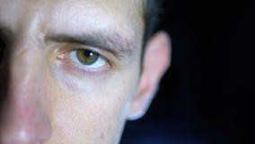Olhar sério de um homem novo que concentrasse trabalhos em um fundo preto Movimento lento filme