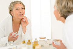 Olhar sênior da mulher nsi mesma espelho do banheiro imagens de stock