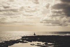 Olhar só do surfista no oceano sob um grande céu nebuloso Fotos de Stock Royalty Free