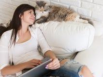 Olhares bonitos da jovem mulher em seu gato imagens de stock