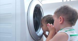 Olhares bonitos das crian?as dentro da m?quina de lavar M?quina de gerencio do cilindro M?quina de lavar da lavanderia do conceit filme