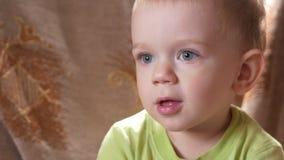 Olhares bonitos de um menino do rapaz pequeno atentamente a certo ponto Sorriso e surpreendido no que viu video estoque