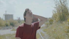 Olhares confusos do menino para trás e no céu na estrada de ferro 4K filme