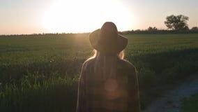 Olhares da jovem mulher de um viajante bonito ou do fazendeiro no por do sol ou no nascer do sol Camisa e chapéu vestindo de mant filme