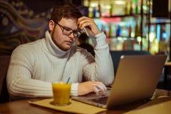 Olhares do homem comprimidos no café com portátil fotografia de stock royalty free