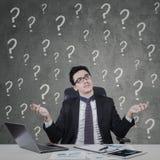 Olhares do homem de negócios confundidos com o sinal da pergunta Fotografia de Stock Royalty Free