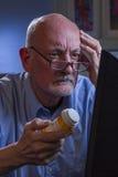 Olhares do homem mais idoso confundidos ao reencher a prescrição em linha, vertical Fotos de Stock