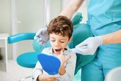 Olhares do menino do dentista e da criança no espelho nos dentes imagens de stock royalty free
