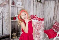 Olhares e sorrisos da menina através do quadro Imagens de Stock