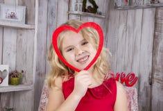 Olhares e sorrisos da menina através do quadro Imagem de Stock Royalty Free