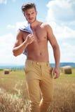 Olhares exteriores do homem em topless em você com a camisa no ombro Foto de Stock Royalty Free