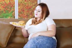 Olhares gordos da mulher confundidos para comer Imagens de Stock Royalty Free