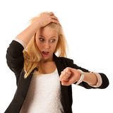 Olhares louros novos da mulher em seu relógio quando for iso atrasado Imagens de Stock Royalty Free