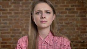 Olhares sérios novos da menina, tentativas a não gritar, tristeza, concepção da emoção, fundo do tijolo video estoque
