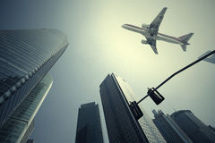 Olhe acima em aviões está voando prédios de escritórios urbanos modernos em S Fotos de Stock