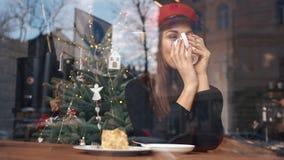 Olhe da parte externa na mulher encantador no café bebendo do chapéu vermelho que senta-se no café confortável video estoque