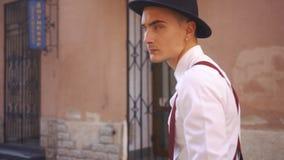 Olhe de trás no homem no chapéu negro que anda ao longo da rua filme