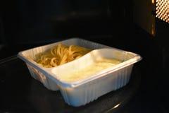 Olhe dentro da micro-ondas Alimento branco empacotado, espaguetes com mussarela e espinafres fotografia de stock