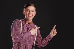 Olhe isto! Homem científico novo considerável no laço da camisa do vintage que aponta o espaço da cópia e que sorri ao estar cont imagens de stock