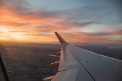 Olhe na asa do aerplane com o céu nebuloso da laranja, o vermelho e o azul Imagens de Stock Royalty Free