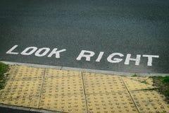 Olhe o sinal direito pintado no asfalto da estrada Fotografia de Stock Royalty Free
