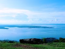 Olhe para fora nas rochas, voe a libélula, veja a represa, e o céu azul com nuvens/pontos cênicos imagens de stock royalty free