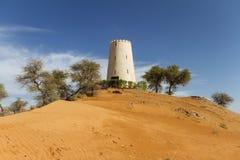 Olhe a torre na duna de areia que cercando com as árvores em Abu Dhabi, UAE Foto de Stock