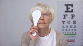 Olho de fechamento envelhecido da senhora e agitação da virada principal com resultado da análise da vista, visão pobre vídeos de arquivo