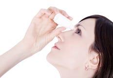 Olho do gotejamento da mulher com gotas de olhos Fotos de Stock