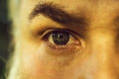 Olho masculino com lente listrada imagem de stock