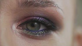 Olho piscar da mulher macro do close-up A beleza compõe do olho verde no movimento lento filme