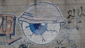 Olho tirado em uma parede de tijolo Pintura mural da cidade Fotografia de Stock